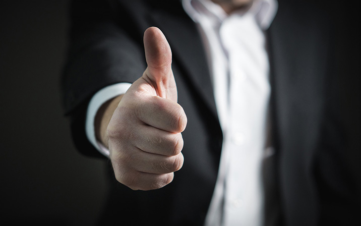 Man in suit gives thumbs up